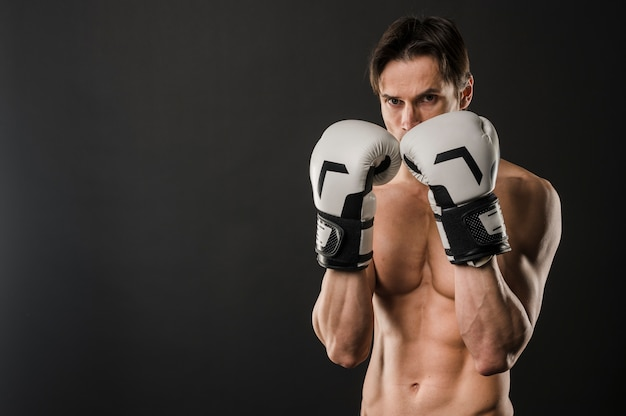 Front view of shirtless muscly man posing with boxing gloves and copy space