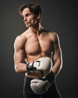 Front view of shirtless muscly man posing with boxing gloves
