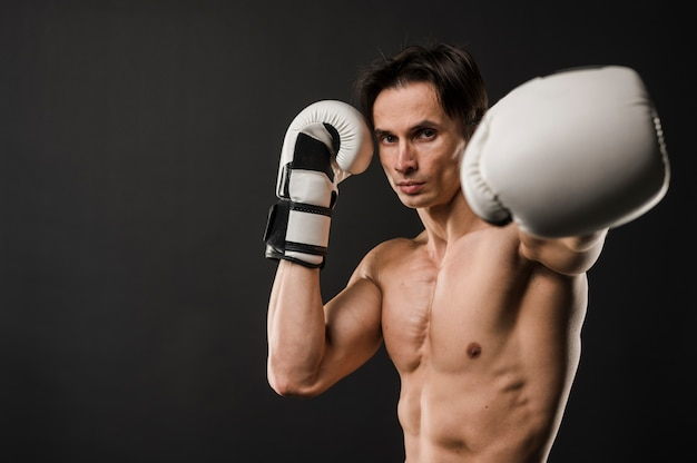 Front view of shirtless muscly man with boxing gloves and copy space
