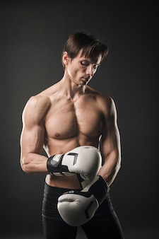 Front view of shirtless muscly man with boxing gloves