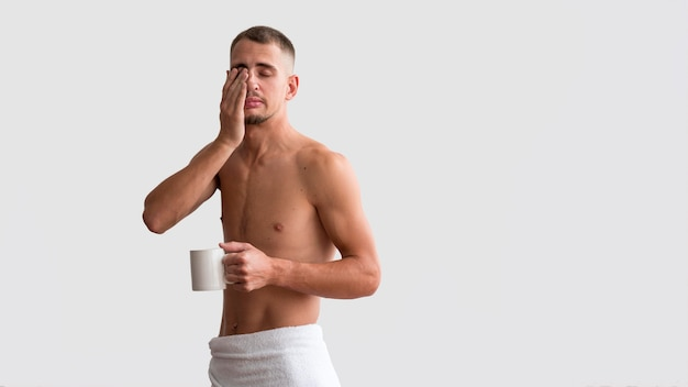 Front view of shirtless sleepy man in the morning with coffee