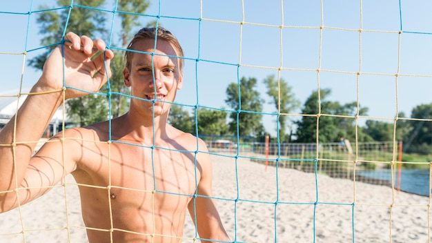 Front view of shirtless smiley male volleyball player posing behind the net