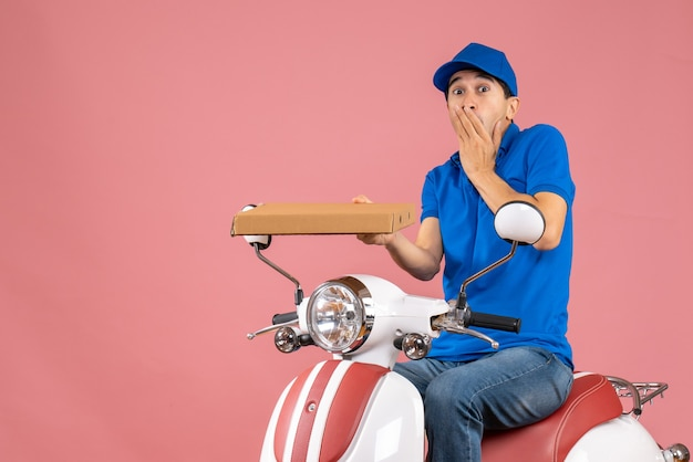 Front view of shocked courier man wearing hat sitting on scooter holding order on pastel peach background