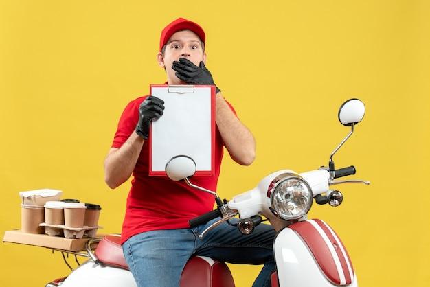 Vista frontale dell'uomo scioccato del corriere che indossa guanti rossi della camicetta e del cappello nella mascherina medica che trasporta l'ordine che si siede sul documento della tenuta dello scooter
