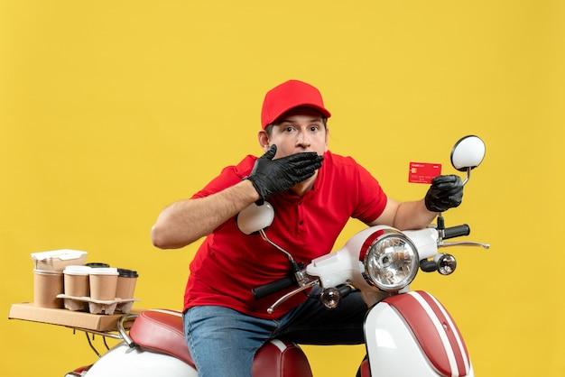 Vista frontale dell'uomo scioccato del corriere che indossa guanti rossi del cappello e della camicetta nella mascherina medica che trasporta l'ordine che si siede sulla carta di credito di puntamento del motorino