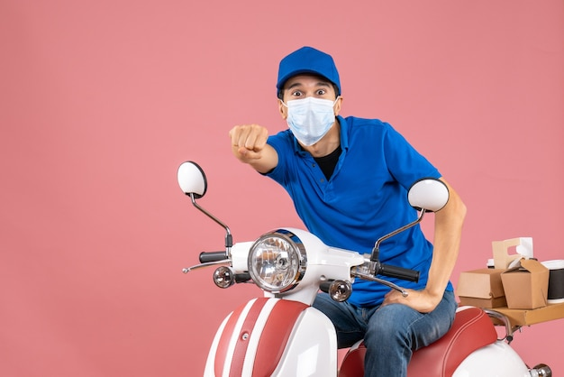 Front view of shocked delivery guy in medical mask wearing hat sitting on scooter on pastel peach background