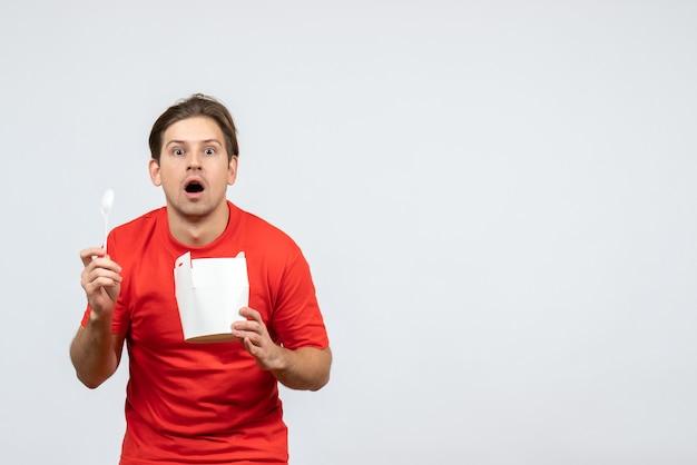 Vista frontale del giovane ragazzo emotivo scioccato in camicetta rossa che tiene la scatola di carta su priorità bassa bianca