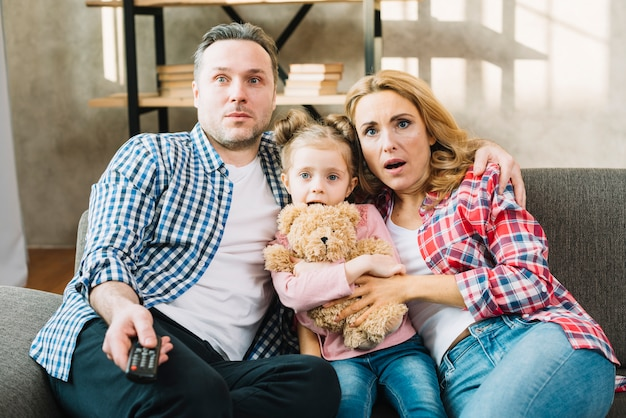 Front view of shocked family watching television in home