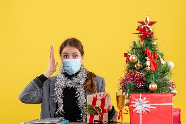 Vista frontale ragazza scioccata con maschera medica seduto al tavolo alzando la mano albero di natale e regali cocktail