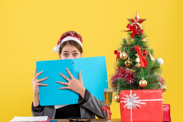 Ragazza scioccata vista frontale con cappello di natale seduto al tavolo che copre il viso con albero di natale cartella documenti e cocktail di regali