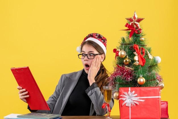 Vista frontale ragazza scioccata con cappello di natale seduto al tavolo guardando file di documento albero di natale e regali cocktail