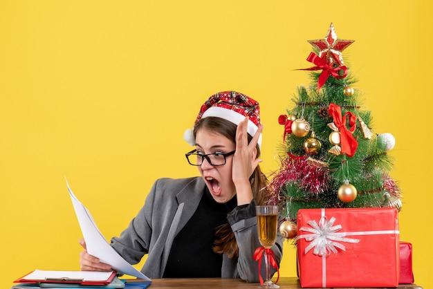 Vista frontale ragazza scioccata con cappello di natale seduto al tavolo guardando carte albero di natale e regali cocktail