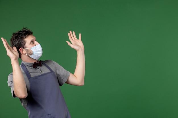 Vista frontale del cameriere scioccato in uniforme con maschera medica e guardando in alto sul lato sinistro sul muro verde