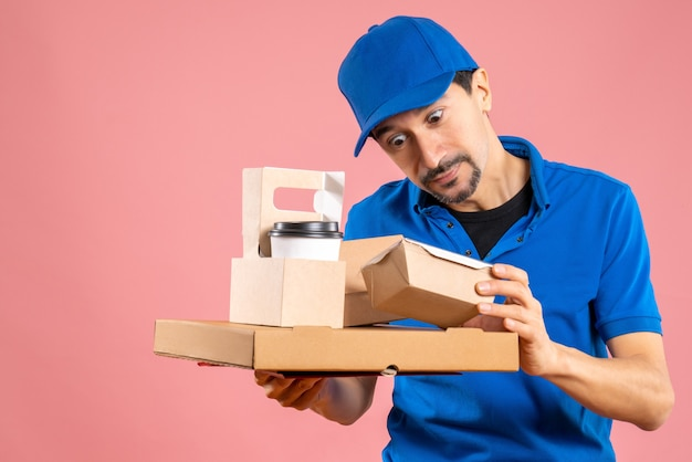Front view of shocked male delivery guy wearing hat showing orders