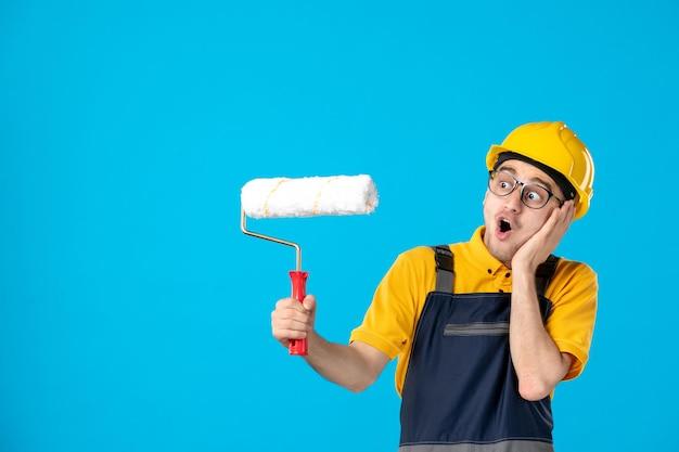 Vista frontale del lavoratore maschio scioccato in uniforme gialla con rullo di vernice sull'azzurro