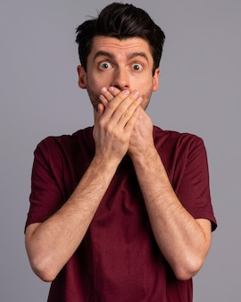 Front view of shocked man covering his mouth