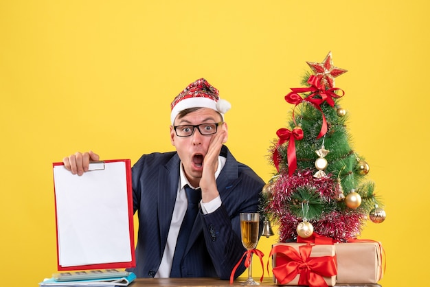 Front view of shocked man holding clipboard sitting at the table near xmas tree and presents on yellow