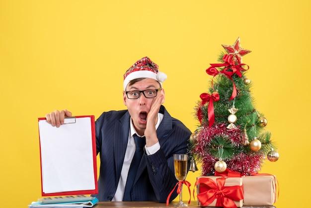 Vista frontale dell'uomo scioccato che tiene appunti seduto al tavolo vicino all'albero di natale e presenta su giallo