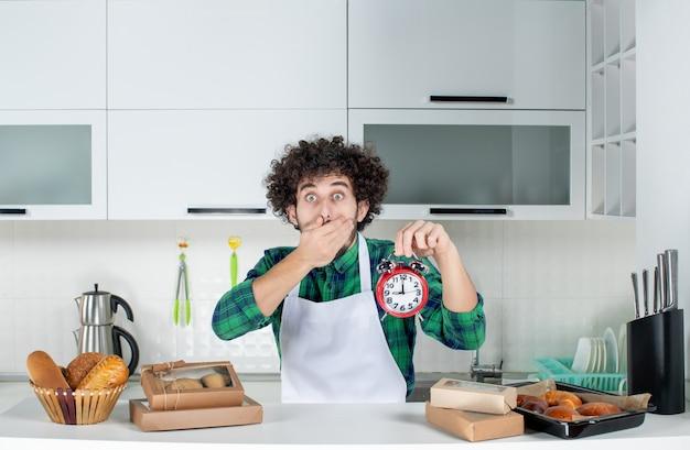 Vista frontale dell'uomo scioccato in piedi dietro il tavolo con vari pasticcini e tenendo l'orologio nella cucina bianca