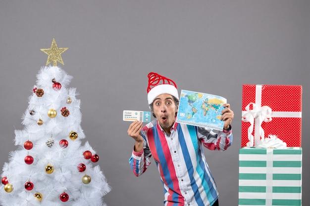 世界地図と旅行チケットを保持しているスパイラルスプリングサンタ帽子を持つ正面図ショックを受けた男