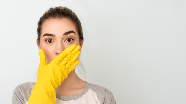 Front view of shocked woman with cleaning glove on hand