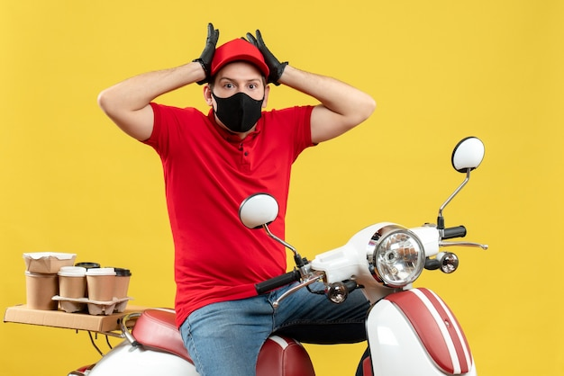 Vista frontale del giovane adulto scioccato che indossa guanti rossi della camicetta e del cappello nella mascherina medica che trasporta l'ordine che si siede sul motorino su fondo giallo