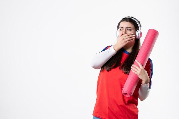 Вид спереди потрясен молодая женщина в спортивной одежде с наушниками