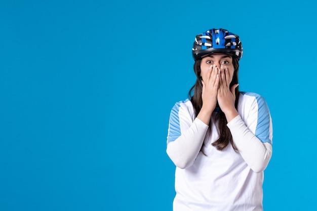 Вид спереди потрясен молодая женщина в спортивной одежде в шлеме