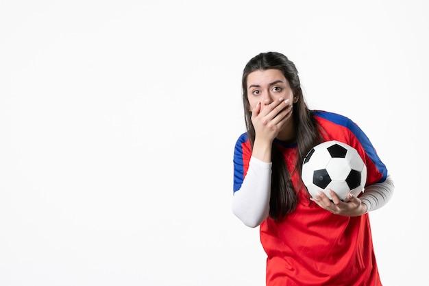Vista frontale scioccata giovane donna in abiti sportivi con pallone da calcio