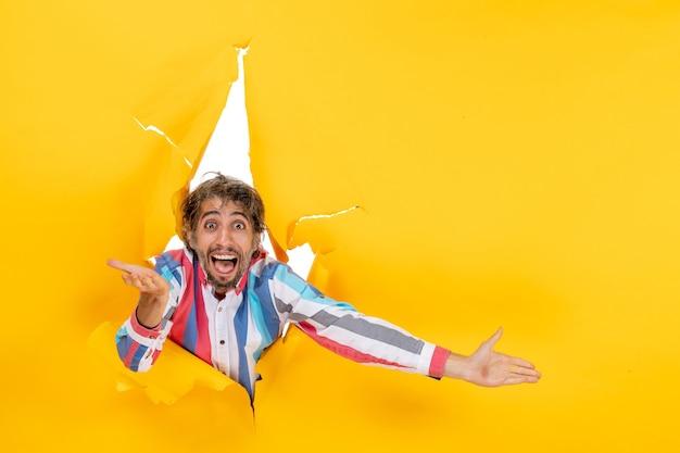 Vista frontale di un giovane scioccato che guarda qualcosa attraverso un buco strappato in carta gialla