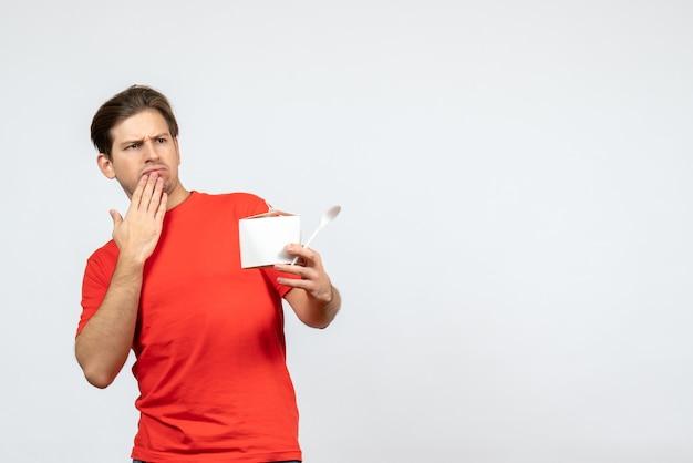 Vista frontale del giovane ragazzo scioccato in camicetta rossa che tiene scatola di carta e cucchiaio su sfondo bianco