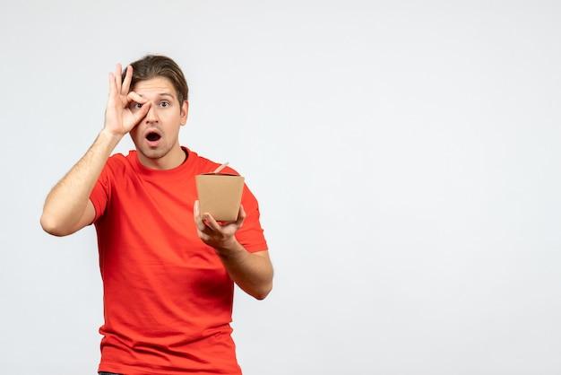 Vista frontale del giovane ragazzo scioccato in camicetta rossa che tiene piccola scatola che fa gesto di occhiali su priorità bassa bianca