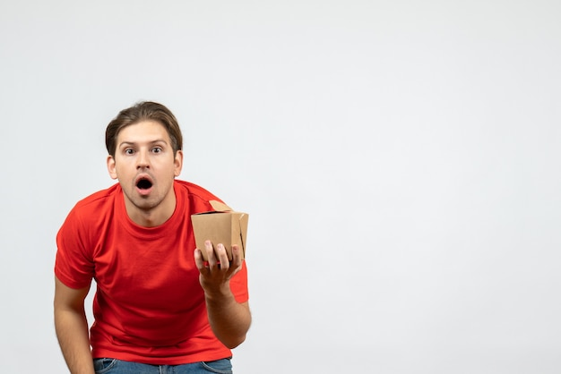 Front view of shocked young guy in red blouse holding small box on white background