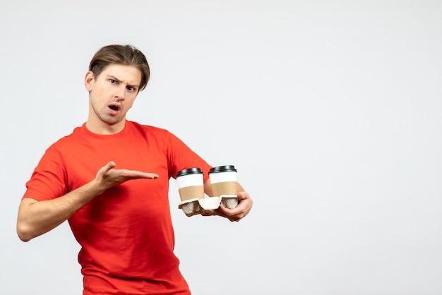 Vista frontale del giovane ragazzo scioccato in camicetta rossa che indica il caffè in bicchieri di carta su sfondo bianco