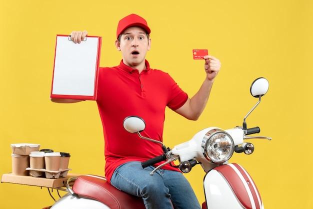 Vista frontale del giovane ragazzo scioccato che indossa camicetta rossa e carta di credito che consegna gli ordini che tengono documento e carta di credito su sfondo giallo