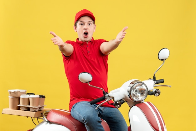 Front view of shocked young guy wearing red blouse and hat delivering orders extending his arms forward on yellow background
