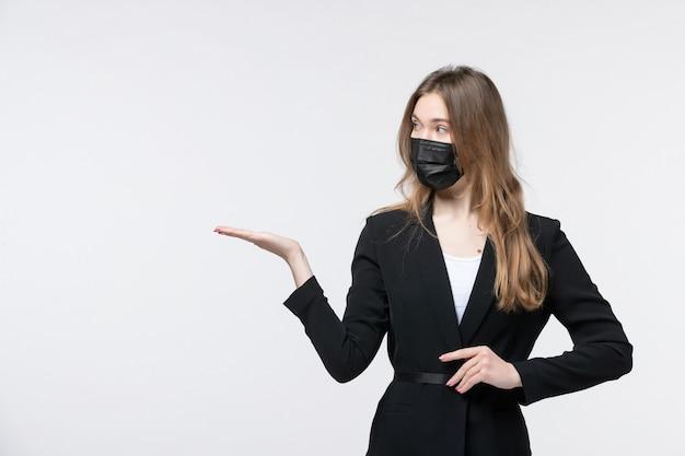 Vista frontale della giovane donna scioccata in tuta che indossa una maschera chirurgica e indica qualcosa su bianco