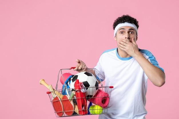 正面図は、スポーツ用品でいっぱいのバスケットとスポーツ服を着た若い男性に衝撃を与えた