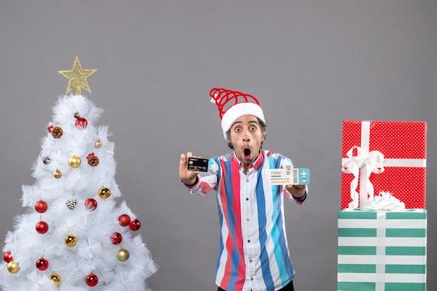 전면보기는 크리스마스 트리와 선물 주위에 카드와 여행 티켓을 들고 충격 젊은 남자
