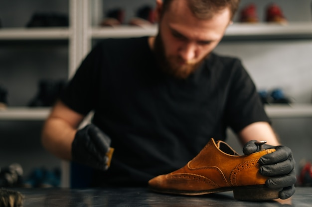 Front view of shoemaker wearing black latex gloves polishing old light brown leather shoes for later...