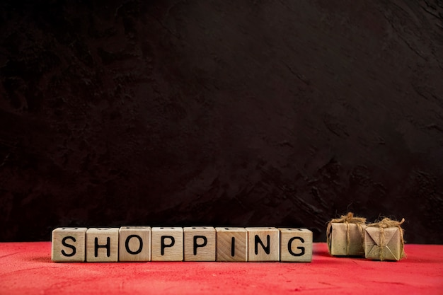 Front view of shopping word on red table