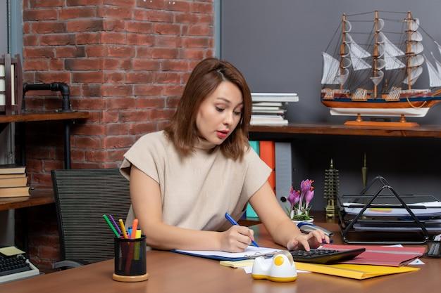Vista frontale del banner donna capelli corti qualcosa usando la calcolatrice seduto al muro
