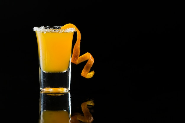 Front view of shot glass with orange cocktail