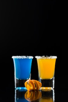 Front view of shot glassed with colored cocktails