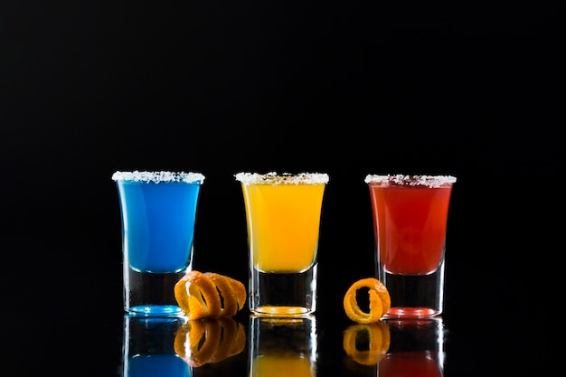 Front view of shot glasses with colorful cocktails