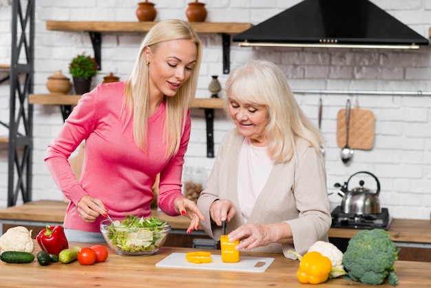 Front view shot of mother and daughter cutting a sweet pepper