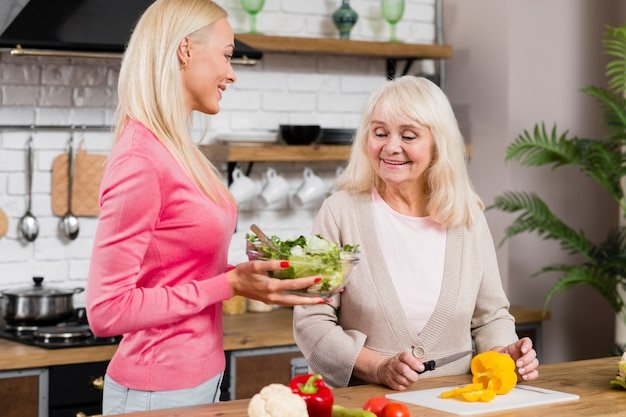 Front view shot of mother and daughter holding a salad