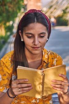 책을 읽고 노란색 셔츠에 여자의 전면 뷰 샷