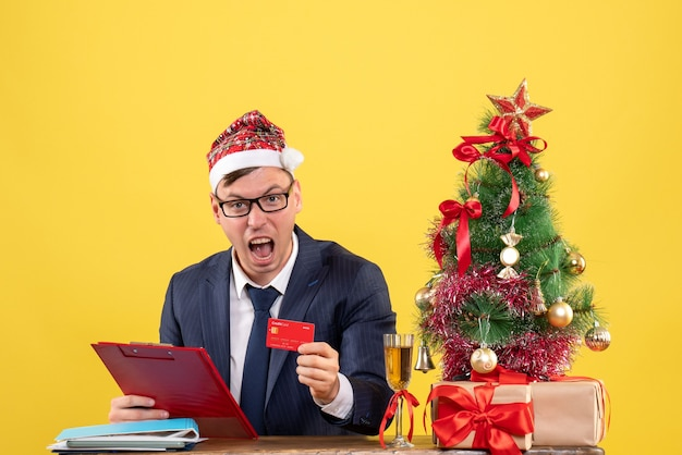 Front view of shouted business man holding clipboard sitting at the table near xmas tree and presents on yellow.