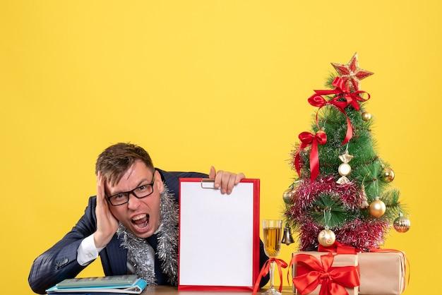 Vista frontale dell'uomo di affari gridato che tiene appunti che si siede al tavolo vicino all'albero di natale e presenta su giallo.